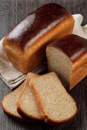 木製の背景上のスライスとライ小麦パン 写真素材