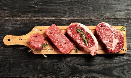 Świeże surowe Prime Black Angus stek z wołowiny na desce: Tenderloin, Denver Cut, Striploin, Rib Eye Zdjęcie Seryjne