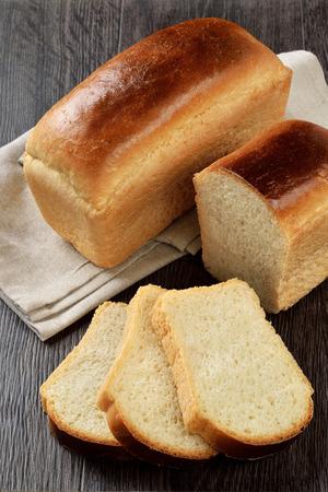 木製の背景上のスライス、パン一斤