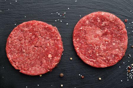 2 新鮮な生プライム ブラック ・ アンガス牛のハンバーガーのパティ黒い石の背景に。平面図です。