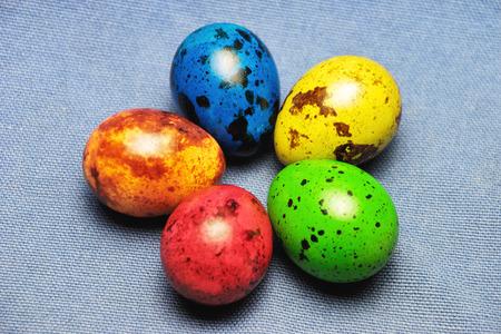 色塗りウズラ青リネンの背景にイースターの卵