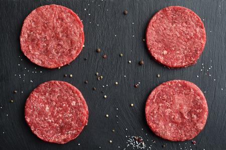 4 新鮮な生プライム ブラック ・ アンガス牛のハンバーガーのパティ黒い石の背景に。平面図です。