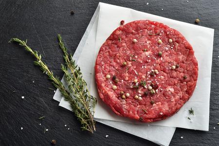 新鮮な生プライム ブラック ・ アンガス牛ハンバーガー パティ黒い石の背景に。平面図です。 写真素材