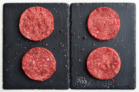 4 新鮮な生プライム ブラック ・ アンガス牛のハンバーガーのパティ黒い石のプレートに。平面図です。 写真素材