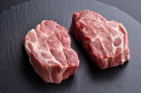 Two fresh raw boneless pork shoulder butt slices on black stone plate