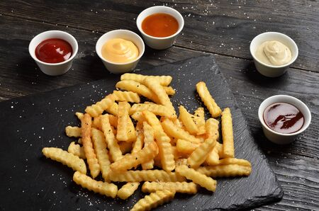 French fries on stone plate with sauces on black wooden background
