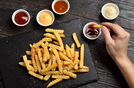 Man's hand dipping french fries in barbecue sauce