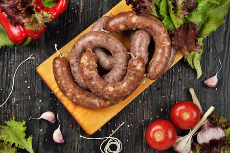 Fresh raw sausages on cutting board. Wooden background. Top view.