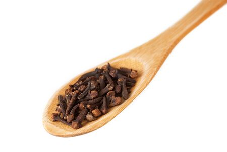 Wooden spoon with cloves isolated on white background 免版税图像
