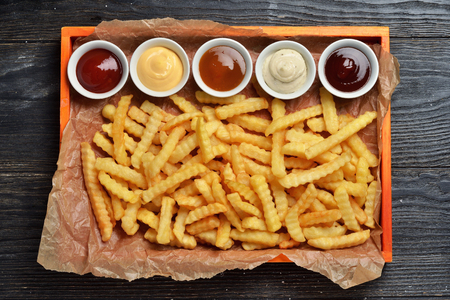French fries on big wooden tray with sauces on black wooden background