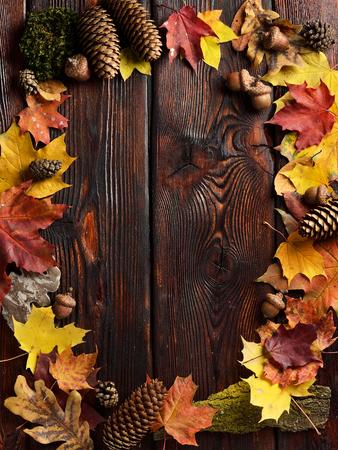 コピースペースを持つ木製の背景に秋の葉のフレーム。トップビュー。