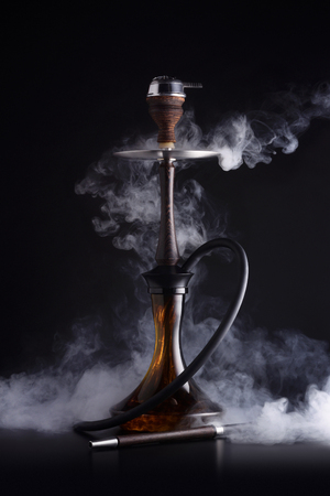 Trendy hookah with cloud of smoke on black background