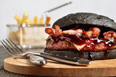 Black Burger with French fries on background. Selected focus.