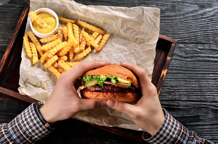 Man hold burger in hands. Meal with burger and french fries.