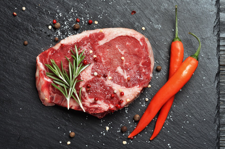 Fresh raw Prime Black Angus Rib Eye beef steak on stone background. Top view.