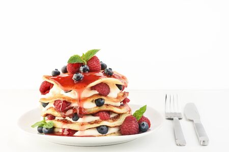 The stack of pancakes on plate with fresh berries