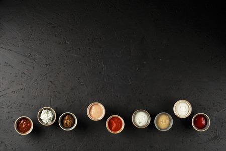 Different types of sauces on black painted OSB plate. Top view.