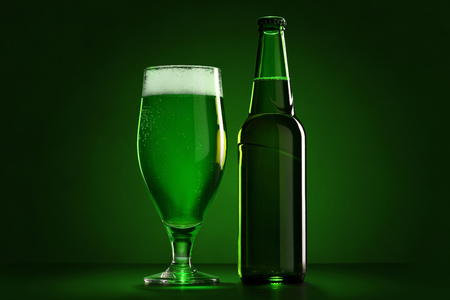 The bottle and the glass of beer on St. Patrick's Day. Green backgroud.