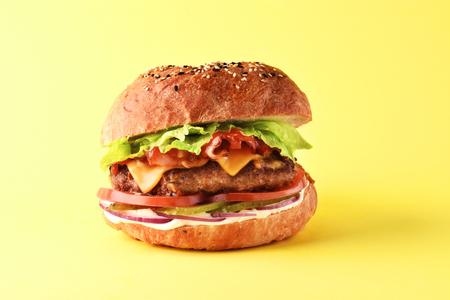 Fresh juicy burger on yellow background