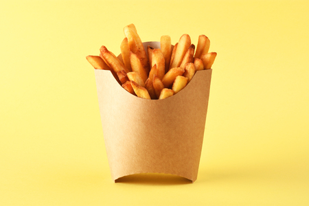 French fries in kraft french fry box on yellow background