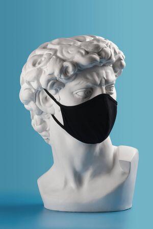 Gypsum David bust head in cloth face mask. Novel coronavirus. Concept of coronavirus quarantine.
