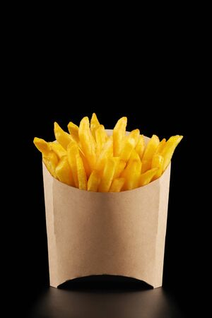 French fries in kraft french fry box on black background with copy space