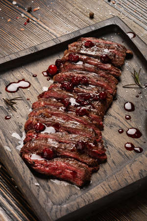 Prime Black Angus Skirt steak with cranberry sauce on wooden board. Medium Rare degree of steak doneness.
