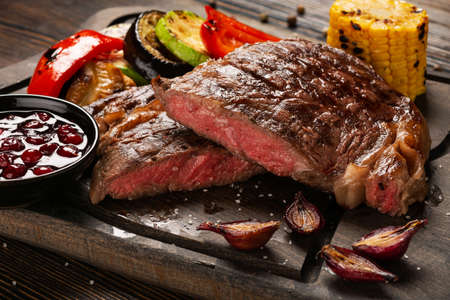 Prime Black Angus Ribeye steak with grilled vegetables and cranberry sauce on wooden board. Medium Rare degree of steak doneness. Selected focus.