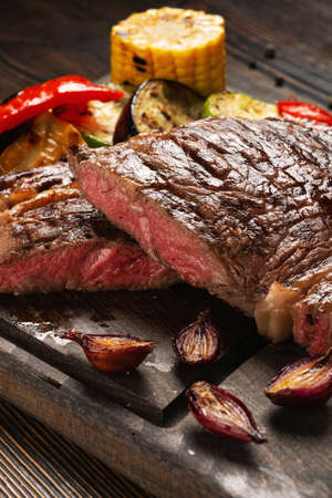 Prime Black Angus Ribeye steak with grilled vegetables on wooden board. Medium Rare degree of steak doneness. Selected focus.