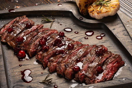 Prime Black Angus Skirt steak with cranberry sauce and grilled garlic on wooden board. Medium Rare degree of steak doneness.