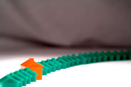 sell out: A curved row of similar green little plastic houses, with one red one sticking out. Shot on white against a grey backdrop. Stock Photo