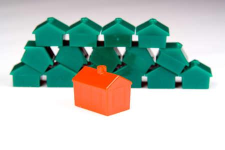 ordelijk: Een kleine rode plastic huis in beeld op de voorgrond, voor een nette en ordelijke stapel soortgelijke groene, in een wazige achtergrond.