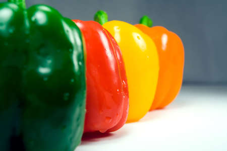 glistening: Four wet peppers (green, red, yellow, orange) in a row, level with the camera, closeup. Only red pepper is in focus, glistening.