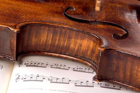 concerto: Un viejo viol�n polvoriento se reclina de lado a trav�s de una cuenta musical. Solamente una l�nea de la m�sica est� en foco. Foto de archivo