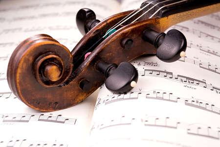 The dusty scroll of an old violin rests in the middle of a musical score. Only one line of music is in focus. Imagens