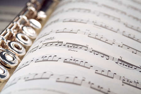 rehearse: A used flute lies along the spine of an open musical score. Only one line of music is in focus.
