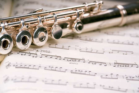 rehearse: A used flute rests across an open musical score. Only one line of music is in focus.
