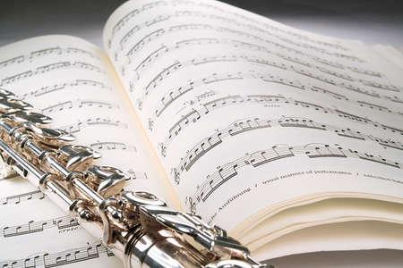 flauta: Una flauta miente transversalmente a trav�s en una cuenta musical abierta contra un fondo gris. El musica se descolora apagado en el fondo. Foto de archivo
