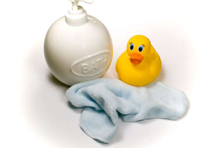 rubbery: A soap dispenser,  wash cloth and yellow rubbery ducky, isolated against a white background with shadows intact.
