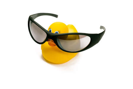 surprising: A bright yellow rubber ducky wearing cool shades isolated against a white background.
