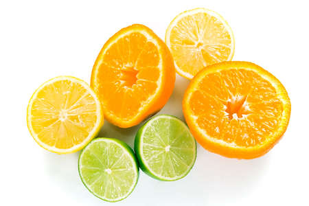 Wet halves of lemons, limes and oranges tumbled in a pile, isolated against a white background.