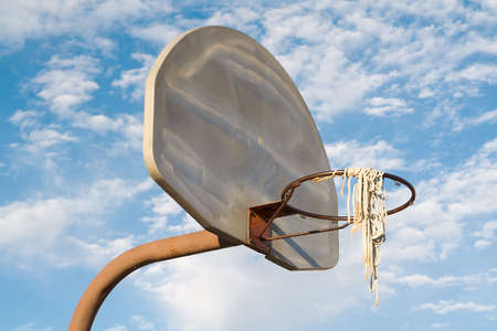 b ball: Vandalized, rusty urban basketball hoop, net, stanchion and backboard, shot against a brilliant blue sky. Stock Photo