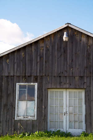 A run-down old farmhouse against a blue sky. photo