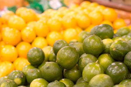 A pile of limes in focus against a blurred background of lemons. Shot at the local grocery store.