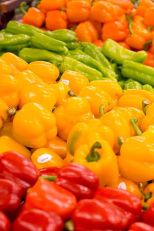 Piles of red, yellow, and orange peppers at the local grocery store. Focus on the yellow peppers.