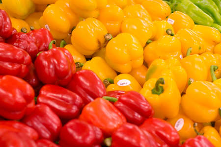 Piles of red and yellow peppers at the local grocery store. Focus on the yellow peppers. Stok Fotoğraf