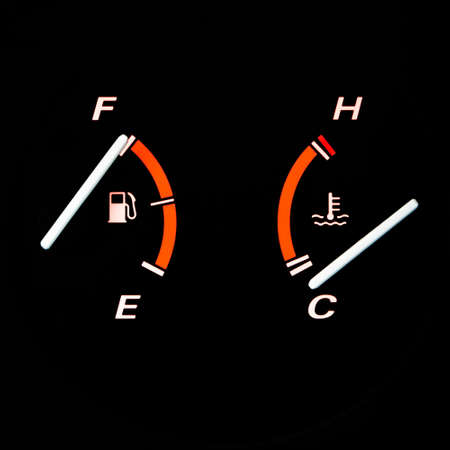 gage: Detail from a glowing car dashboard: fuel and engine temperature guages.