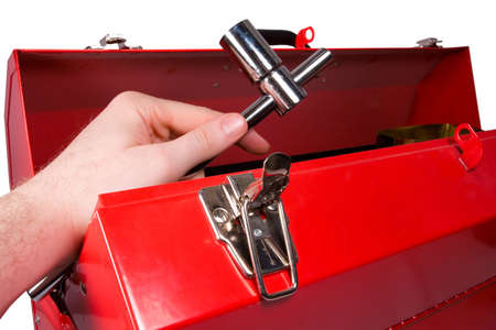 yourself: A hand removing a socket wrench from a red metal toolbox, isolated against white background. Stock Photo