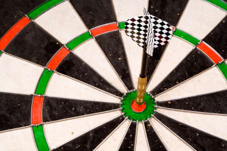 A dart in the bullseye. Checkered fletchings of dart in focus.