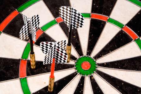 Three darts missing the bullseye. Checkered fletchings in focus. Stock Photo